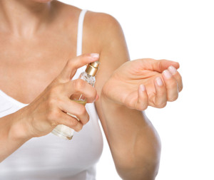Closeup on young woman applying perfume on hand
