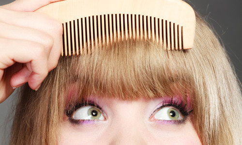 Fashion Beauty And Haircare Concept. Closeup Young Woman Refreshing Her Hairstyle Girl Combing Her Hair Fringe With Wooden Comb